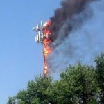 cell tower afire above tree line